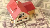 Toy house with red tiled roof on dollars bank notes, rotates