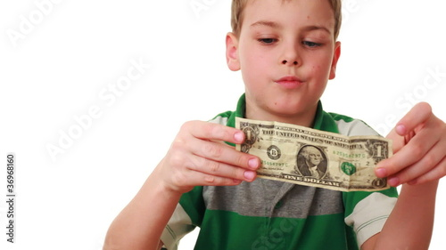 boy carefully studies bill denominations of one dollar