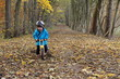 Kind fährt mit Laufrad durch Blätter