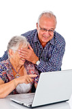 Seniors couple using a computer laptop
