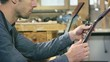 Young man working as craftsman in italian guitar workshop