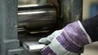 Man repeatedly inserts metal plate in rolling machine