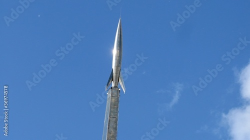 Monument to rocket on sky background