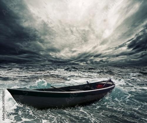 Leinwanddruck Bild Abandoned boat in stormy sea