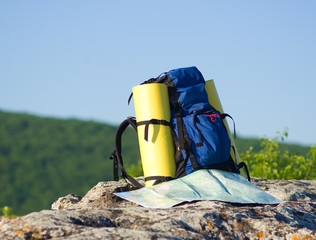 Backpack and map in mountain.nature composition.
