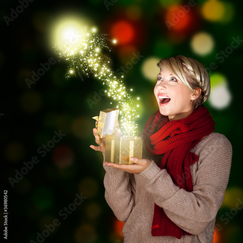 junge blonde Frau öffnet Geschenk mit magischem Inhalt