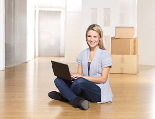 young woman working with notebook, just moved to new apartment