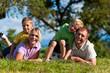 Familie mit Kindern und Fußball auf einer Wiese