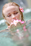 Beautiful woman bathing in pool with frangipani flowers