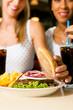 Zwei Frauen essen Hamburger und trinken Cola