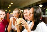 Friends eating fast food in a restaurant
