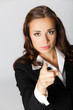 Serious business woman pointing finger at viewer