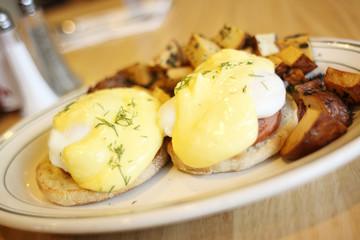 Delicious eggs benedict with seasoned potatoes for breakfast.