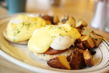 Delicious eggs benedict with seasoned potatoes for breakfast.