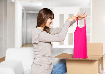 Young Woman opening parcel with cloths