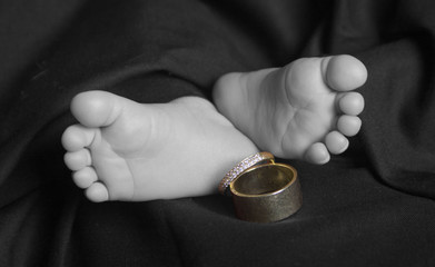 Baby feet with wedding rings black and white selective color