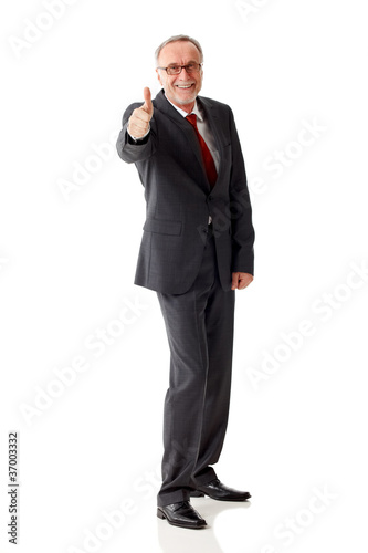Standing mature business man with thumbs up