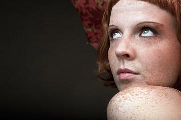 Junge rothaarige Frau vor schwarzem Hintergrund