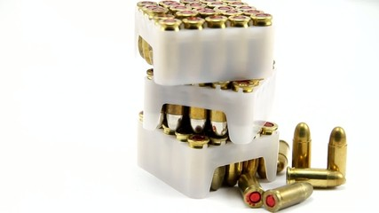 Pile of gun bullets boxes rotating on white