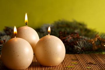 Weihnachtskerze vor grünem Hintergrund ©yvonneweis