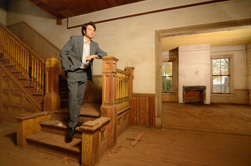 Man Standing on Stairs in an Old House
