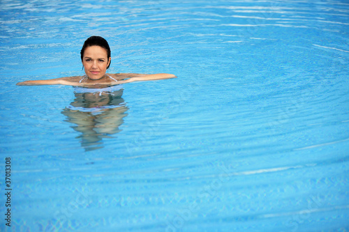 Brunette alone in swimming pool