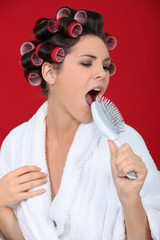 Woman with hair rollers singing into brush