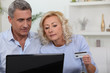 Older couple using a credit card online