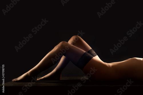 Beine einer nackten Frau in halterlosen Strümpfen
