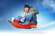 Cool young man fly on a sled in the snow
