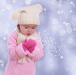 Little girl blowing snowflakes from her hands