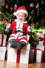 Crying little boy with gift boxes