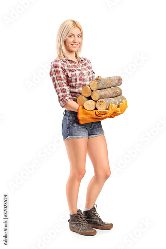 Portrait of a young craftswoman holding fire wood