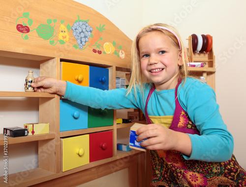 Kleines Mädchen spielt im Kaufmannsladen