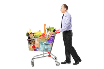 Person pushing a shopping cart full with groceries