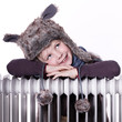 Cute girl with pelt cap leans over a radiator