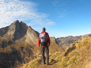 Wanderer mit Rucksack auf alpinem Höhenweg