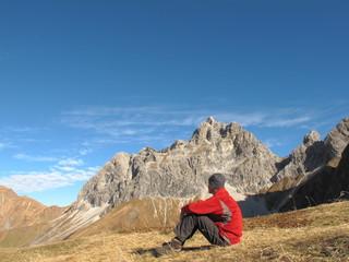 Wanderer sitzt und geniesst Aussicht