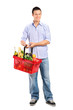 Portrait of a young male holding a full shopping basket