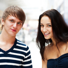 Portrait of young couple embracing at shopping mall and looking