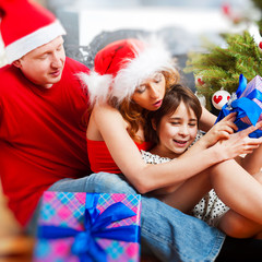 Young happy familye near a Christmas tree at home holding gift a