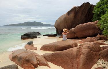 femme sur plage de sable blanc et rochers aux seychelles