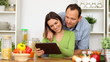 Young happy couple with tablet computer by the table in kitchen