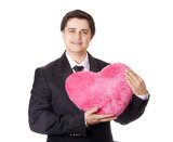 A man holding toy heart in formal black tux with tie isolated on poster