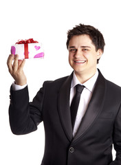 A man holding present box in formal black tux