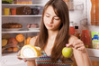 young woman with apple and cake on background fridge