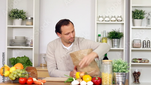 man unpacking vegetables from paper shopping bag in kitchen