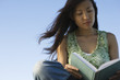 Woman reading book outdoors, hair blowing in breeze
