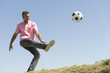 Man playing with soccer ball outdoors, smiling