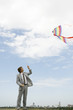 Businessman flying kite in field
